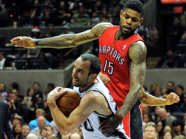 Manu Ginobili of the Spurs eludes Amir Johnson of the Toronto Raptors on his way to a layup during which he was fouled at the AT&T Center on Wednesday, Dec. 26, 2012. Ginobili scored on the ensuing free throw to complete a three-point play. Photo: Billy Calzada, San Antonio Express-News / SAN ANTONIO EXPRESS-NEWS