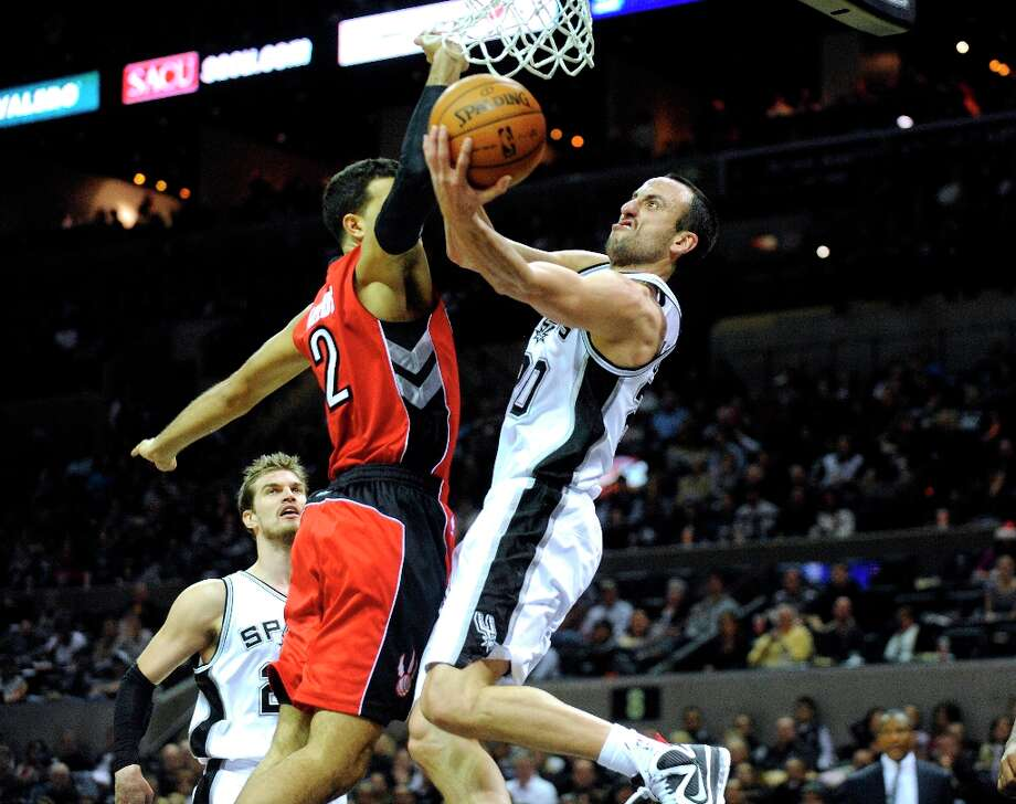 Manu Ginobili of the Spurs is fouled by Landry Fields of the Toronto Raptors as he scores on a layup on Wednesday, Dec. 26, 2012. Ginobili scored on the ensuing free throw to complete a three-point play. Photo: Billy Calzada, San Antonio Express-News / SAN ANTONIO EXPRESS-NEWS