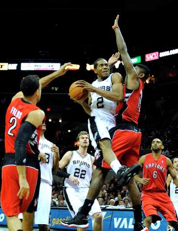 Kawhi Leonard (2) of the Spurs drives to the basket as Amir Johnson of the Toronto Raptors defends during second-half action at the AT&T Center on Wednesday, Dec. 26, 2012. Photo: Billy Calzada, San Antonio Express-News / SAN ANTONIO EXPRESS-NEWS