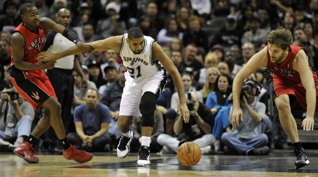 Spurs forward Tim Duncan (center) tries to get a loose ball in front of Toronto Raptors players Terrence Ross (left) and Aaron Gray (right) during the first half on Wednesday, Dec. 26, 2012, in San Antonio. Photo: Bahram Mark Sobhani, Associated Press / FR91484 AP