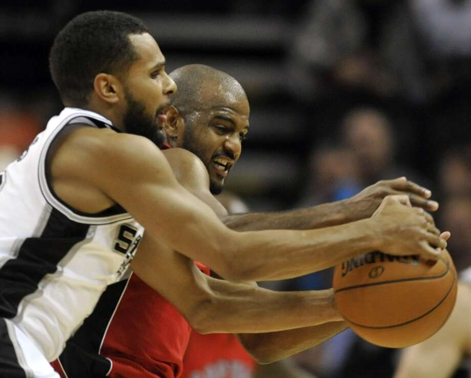 Spurs guard Patty Mills (left) and Toronto Raptors guard John Lucas III fight for control of the ball during the second half on Wednesday, Dec. 26, 2012, in San Antonio. The Spurs defeated the Raptors 100-80. Photo: Bahram Mark Sobhani, Associated Press / FR91484 AP