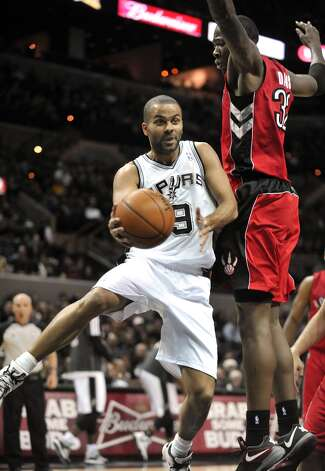 Spurs guard Tony Parker drives against Toronto Raptors forward Ed Davis during the first half on Wednesday, Dec. 26, 2012, in San Antonio. Photo: Bahram Mark Sobhani, Associated Press / FR91484 AP