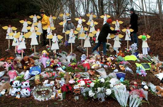 Georgia Hendren, left, Reilly Hendren, along with their mother, Jennifer Hendren, and father Jim Hendren, place prayer flags from Nepal on angels at a memorial site Saturday, Dec. 22, 2012, honoring the 26 who were killed at Sandy Hook Elementary School in Newtown Friday, December 14. The school was evacuated after Adam Lanza opened fire killing 26 individuals, 20 whom were children. ( Cody Duty / Hearst Newspapers ) Photo: Cody Duty, Cody Duty/Hearst Newspapers / The News-Times