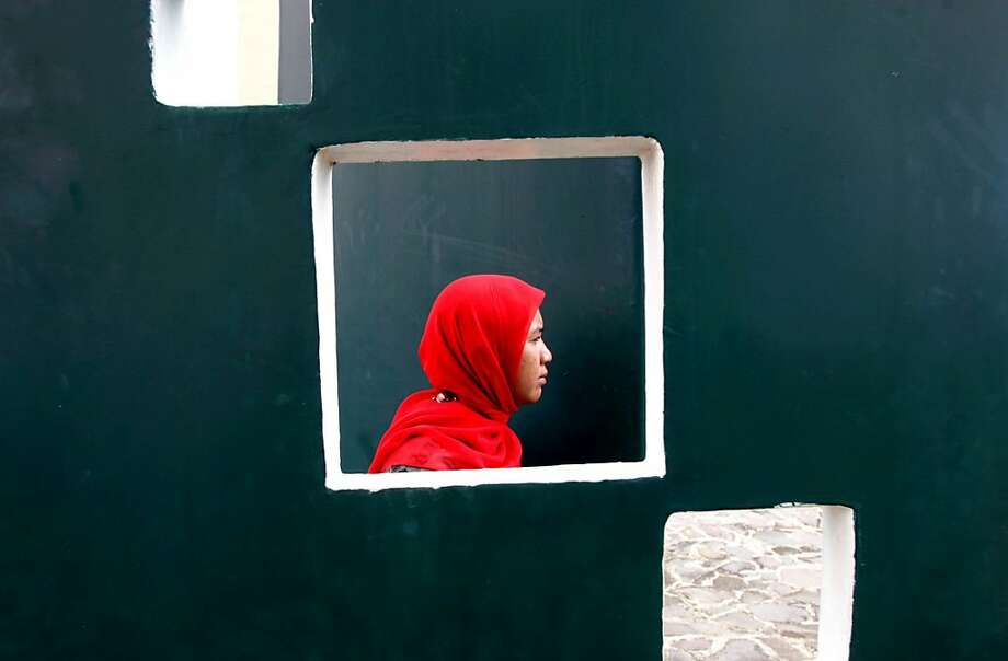 An Acehnese woman is seen through an opening on a wall as she attends a prayer commemorating the 8th anniversary of the Indian Ocean tsunami in Banda Aceh, Aceh province, Indonesia, Wednesday, Dec. 26, 2012. The disaster killed more than 100,000 people in the province. Photo: Heri Juanda, Associated Press