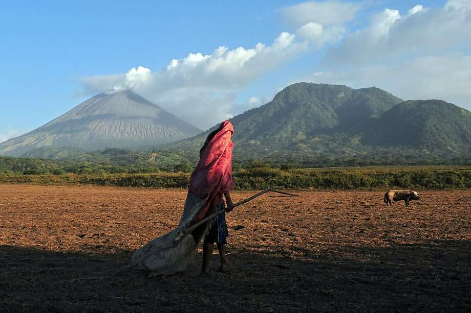 A man walks in a field in Grecia 4, Chinandega, 150 km from Managua, with the San Cristobal volcano in the background on December 26, 2012. The San Cristobal volcano began spewing smoke and ashes Tuesday afternoon. Photo: Hector Retamal, AFP/Getty Images