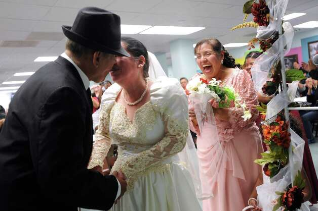 Jesse Talamantes kisses his bride, Velia Estrada, during their wedding ceremony at the San Antonio Lighthouse for the Blind on Friday, Oct. 19, 2012. Alicia Romero, the matron of honor, reacts. The couple met 12 years ago while working at the facility. They got engaged 8 months ago and married before co-workers, friends and family. Talamantes, who has only partial peripheral vision in one eye, can often be found leading and caring for Estrada, who is completely blind. The couple is honeymooning at the Holiday Inn Riverwalk, which donated a two-night honeymoon package. Photo: Billy Calzada, San Antonio Express-News / © 2012 San Antonio Express-News