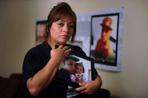 "Irene Solis, whose son, Isaac Champion, was killed in an incident classified as ""justified homicide,"" holds a portrait of him with his daughter, Channel, on Thursday, Aug. 16, 2012. Photo: Billy Calzada, San Antonio Express-News / © San Antonio Express-News"