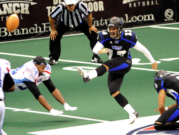 San Antonio Talons kicker Stefan Demos kicks a 33-yard field goal at the end of the first half as Mike Robinson of the Kansas City Command attempts to block it despite losing his helmet during Arena Football League action in the Alamodome on Saturday, June, 30, 2012. Photo: Billy Calzada, San Antonio Express-News / © 2012 San Antonio Express-News