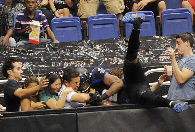 San Antonio Talons receiver Derek Lee falls out of the arena an dinto fans, but holds on to a touchdown pass during Arena Football League action against the Kansas City Command in the Alamodome on Saturday, June, 30, 2012. Photo: Billy Calzada, San Antonio Express-News / © 2012 San Antonio Express-News