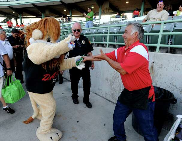 Daren the Lion, mascot of the Bexar County Drug Abuse Resistance Education (D.A.R.E.) program, exchanges gifts with vendor Gonzalo Rincon Jr. before the Frisco Roughriders at San Antonio Missions baseball game at Wolff Stadium on Thursday, Aug. 23, 2012. Area law enforcement agencies and mascots met with fans to promote goodwill and the upcoming National Night Out. Photo: Billy Calzada, San Antonio Express-News / © San Antonio Express-News