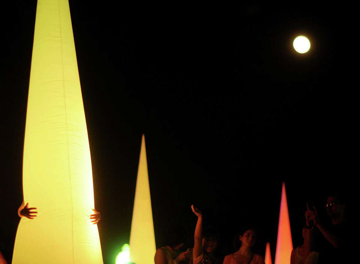 A person hugs a lighted cone display as the super full moon shines overhead during Luminaria 2012 in Hemisfair Park on Saturday, May 5, 2012.