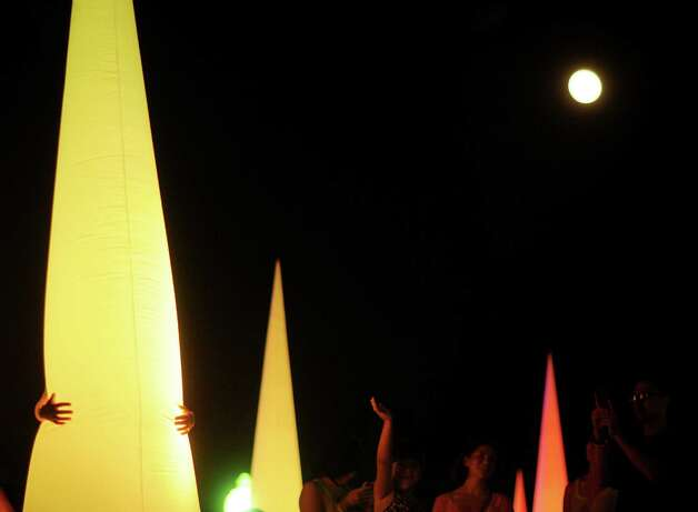 A person hugs a lighted cone display as the super full moon shines overhead during Luminaria 2012 in Hemisfair Park on Saturday, May 5, 2012. Photo: Billy Calzada, San Antonio Express-News / SAN ANTONIO EXPRESS-NEWS