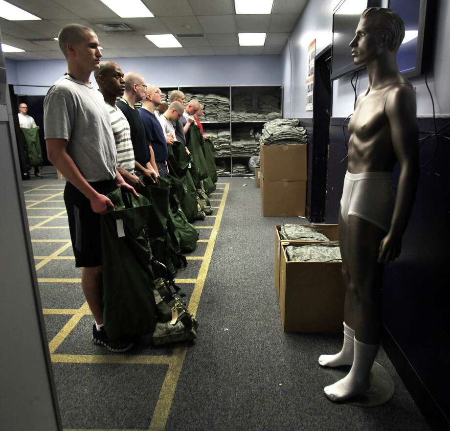 A manikin, right, shows what trainees need to strip down to before they enter a 3-D Body Scanner to determine clothes sizes. The first 72 hours of basic training at Lackland AFB is called Zero Week, when trainees learn to march and speak the Air Force way of life. Thursday, April 19, 2012. Photo: BOB OWEN, San Antonio Express-News / © 2012 San Antonio Express-News