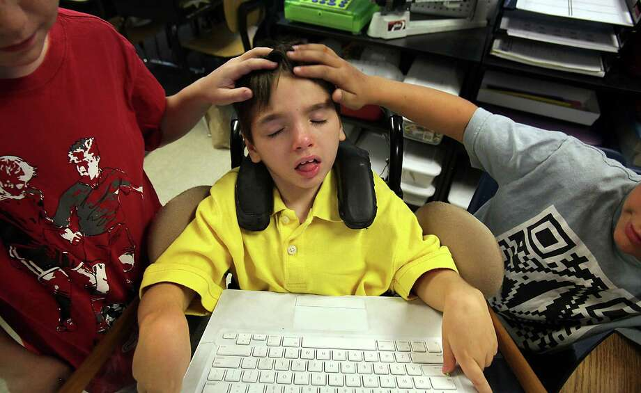 Fellow fourth graders Carter Ulbrich, left, and Scott Mejia, right, rub Conrad Tullis's head after he pushed a button on the computer they use with an educational program. Touch is one way to get a response from Tullis who suffered severe brain injury in a near drowning accident in 2004. The boys go to school at Cambridge Elementary School. Tuesday, April 10, 2012. Photo: BOB OWEN, San Antonio Express-News / © 2012 San Antonio Express-News