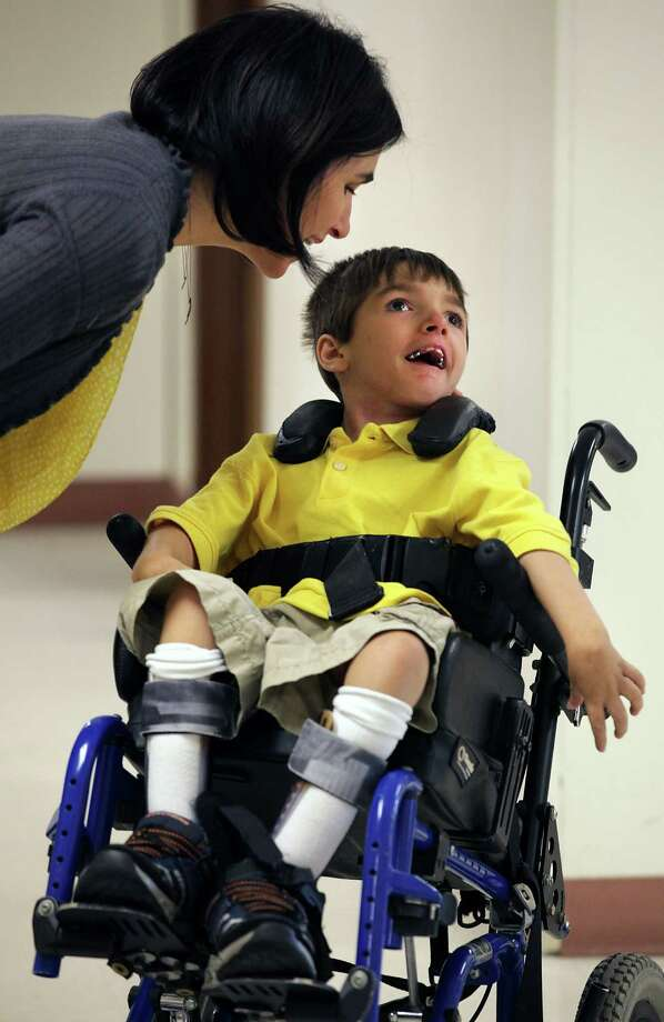 Conrad Tullis, 9, smiles as his mother Liz Tullis speaks closely to him before she leaves him at school. Tullis suffered severe brain injury in a near drowning accident when he was a toddler. He goes to school at Cambridge Elementary School. Tuesday, April 10, 2012. Photo: BOB OWEN, San Antonio Express-News / © 2012 San Antonio Express-News
