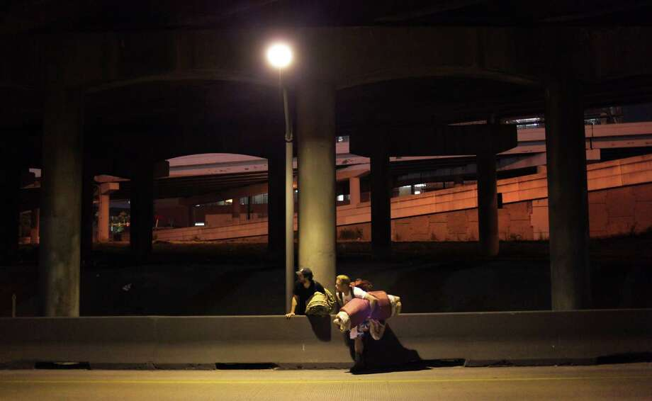 Gavin Rogers, Youth Minister at Trinity Baptist Church, left, and Joshua Burris, a homeless person, watch for traffic on a ramp to I-10 as they carry their bed rolls in downtown San Antonio on their way to sleep under a bridge. Rogers gave up sleeping at home for Lent, to sleep with the Homeless on the streets. Thursday, April 5, 2012. Photo: BOB OWEN, San Antonio Express-News / © 2012 San Antonio Express-News