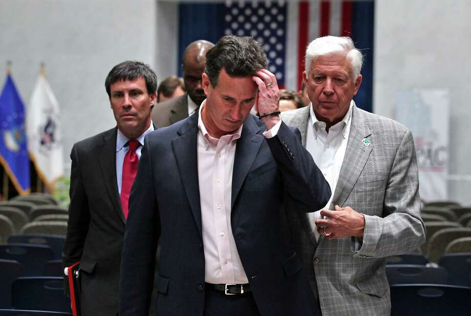 Republican presidential candidate, Rick Santorum, appears pensive, on his way to address the media following his speach to supporters at USAA, Thursday, March 22, 2012. At left is Greg Rothman, a Santorum Advisor, and at right is Foster Friess, multi-millionaire who helps fund the Super PAC Red White and Blue Fund. Photo: BOB OWEN, San Antonio Express-News / © 2012 San Antonio Express-News