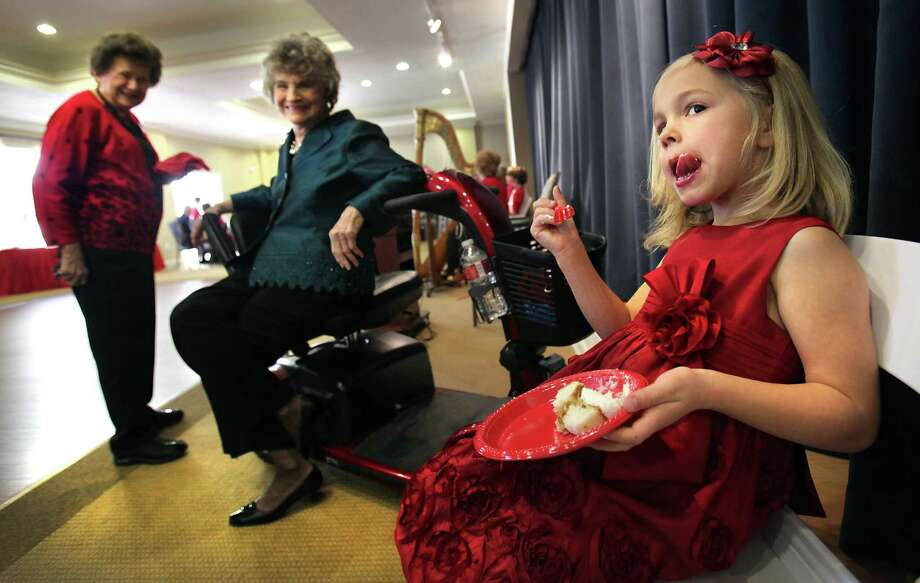 Mabry Munn, right, licks iceing off her lip during a reception following a renewing wedding vows ceremony on Valentine's Day at Franklin Park Sonterra Senior Living Community. Watching the 5 yrs old that was asked to be the flower girl for the service, are her great grandmother Gerry Presley, center, and Norma Uhles, left. Tuesday, Feb. 14, 2012. Photo: BOB OWEN, San Antonio Express-News / © 2012 San Antonio Express-News