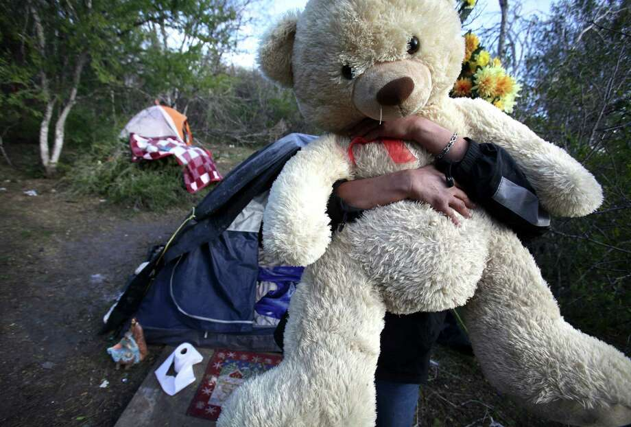 A homeless woman hugs her teady bear outside her tent at a homeless camp near Goliad Rd. and SE Military Dr., Thursday, Jan. 12, 2012. Photo: BOB OWEN, San Antonio Express-News / rowen@express-news.net