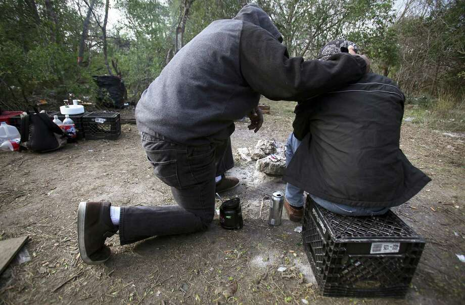 Ron Brown, left, Prospect Courtyard Liaison at Haven for Hope, comforts a homeless man with prayer when he began crying as he sat by his campfire, near Goliad Rd. and SE Military Dr., Thursday, Jan. 12, 2012. Photo: BOB OWEN, San Antonio Express-News / rowen@express-news.net