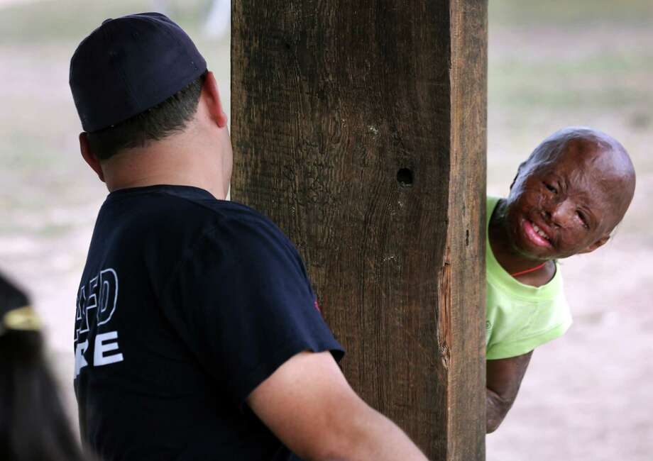 Sean Bigelow, right, 11, of Dallas, plays hide and seek with San Antonio Fire Fighter James Rios at Camp David. Campers from all over Texas take part in the Texas Burn Survivor Society's Pediatric Burn Camp, called Camp David, held at Texas Lion's Camp in Kerrville. Wednesday, July 18, 2012. Photo: Bob Owen, San Antonio Express-News / © 2012 San Antonio Express-News