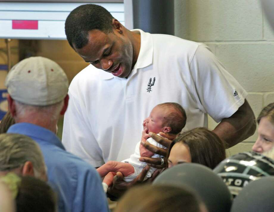 Former San Antonio Spurs David Robinson holds the newest Spurs fan, Cruz Guerra, 18 days old, whose mother, Lacy Cain is a resident at Haven for Hope. Robinson and the Spurs held a rally for the Spurs at Haven for Hope. Wednesday, May 23, 2012. Photo: Bob Owen, San Antonio Express-News / © 2012 San Antonio Express-News