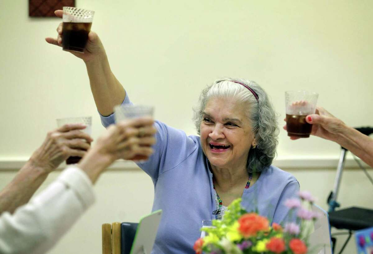 Janie C. lifts her glass of tea in a toast with other seniors at Grace Place Alzheimer's Center as they celebrate Mother's Day with a