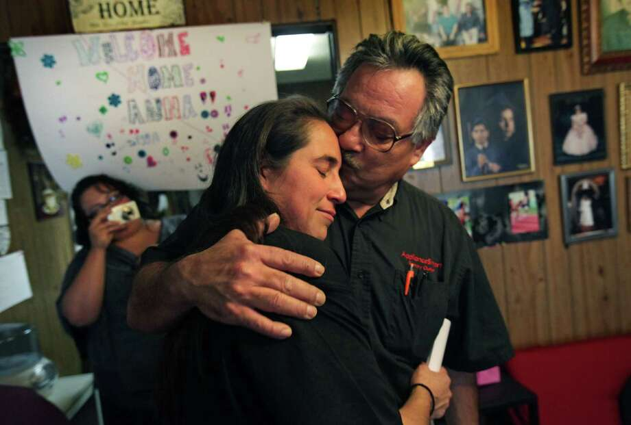 Anna Vasquez hugs one of her older brothers, Robert Vasquez, as they embrace each other for the first time in 12 and a half years. Anna, one of the four San Antonio women fighting to clear their names in the 1994 sexual assault of two sisters, was released from prison on parole from the Crain Unit in Gatesville, TX .  At left is Rose Vasquez, Anna's sister-in-law, taking pictures. Friday, Nov. 2, 2012.Click to browse all of the EN's most memorable photos of 2012  Photo: Bob Owen, San Antonio Express-News / © 2012 San Antonio Express-News