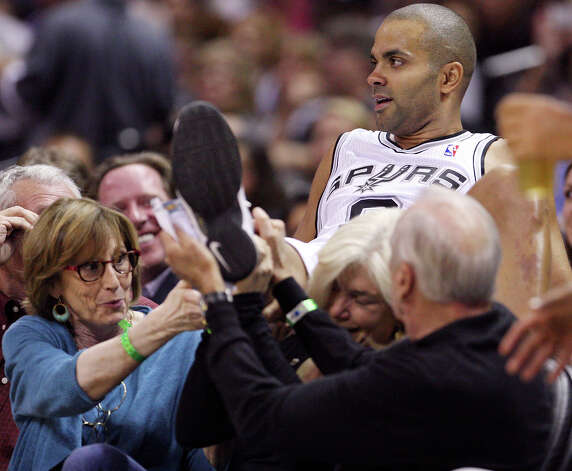 San Antonio Spurs' Tony Parker is helped by fans after landing in their seats while chasing a loose ball during second half action against the Indiana Pacers Monday Nov. 5, 2012 at the AT&T Center. The Spurs won 101-79. Photo: Edward A. Ornelas, San Antonio Express-News / © 2012 San Antonio Express-News