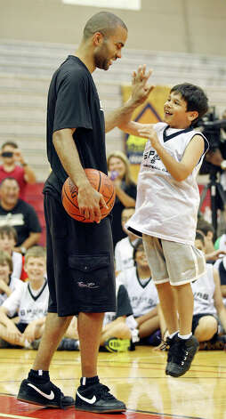 Spurs' Tony Parker (left) high-fives Andrew Trevino, 8, during the Spurs Basketball Camp held at the University of the Incarnate Word Monday June 11, 2012. Photo: Edward A. Ornelas, San Antonio Express-News / © 2012 San Antonio Express-News
