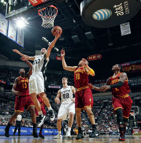 San Antonio Spurs' Manu Ginobili shoots between Cleveland Cavaliers' Tristan Thompson (from left), Anthony Parker, and Kyrie Irving as teammate Tiago Splitter looks on during first half action Sunday April 22, 2012 at the AT&T Center. Photo: EDWARD A. ORNELAS, San Antonio Express-News / © SAN ANTONIO EXPRESS-NEWS (NFS)