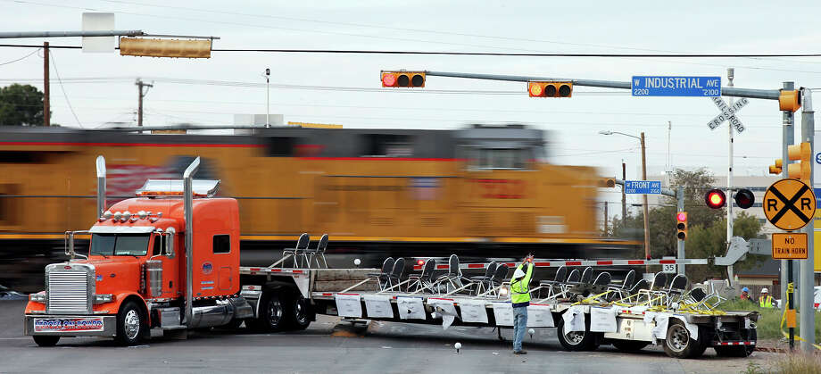 A worker photographs the scene of the crash, Friday Nov. 16, 2012, involving a Union Pacific train and a parade float carrying military veterans in Midland, Tx. as a train passes. Four veterans were killed in the accident. Photo: Edward A. Ornelas, San Antonio Express-News / © 2012 San Antonio Express-News