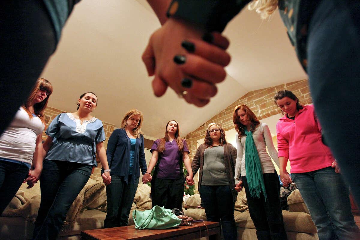 Women pray during a meeting of Lavish Ministry at Kayla Moilanen's home Thursday Nov. 29, 2012.