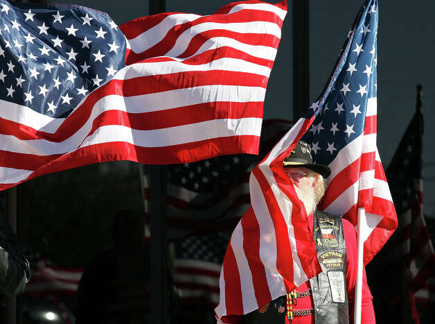Patriot Guard Rider Bob Wall, 65 of Amarillo, Tx., holds an American flag outside the Cornerstone Church during the funeral service for retired Army Sgt. Joshua Michael Saturday Nov. 24, 2012 in Amarillo, Tx. Michael was one of four veterans killed when a train struck a parade float that he, his wife Daylyn Michael (not pictured) and others were riding on, Thursday Nov. 15, 2012 in Midland, Tx. Photo: Edward A. Ornelas, San Antonio Express-News / © 2012 San Antonio Express-News