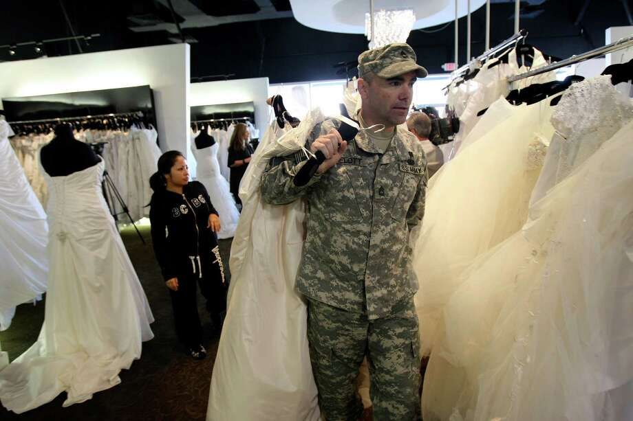 Sgt. 1st Class Mitch Melott carries a wedding down for his fiancee Brandi Ott as Impression Bridal gave away 50 wedding dresses on Tuesday Jan. 10, 2012 to women in the military or who are marrying a military man.  The event is being conducted by the salon and Brides Across America, a non profit group that helps provide wedding gowns to the military. Photo: HELEN L. MONTOYA, San Antonio Express-News / SAN ANTONIO EXPRESS-NEWS