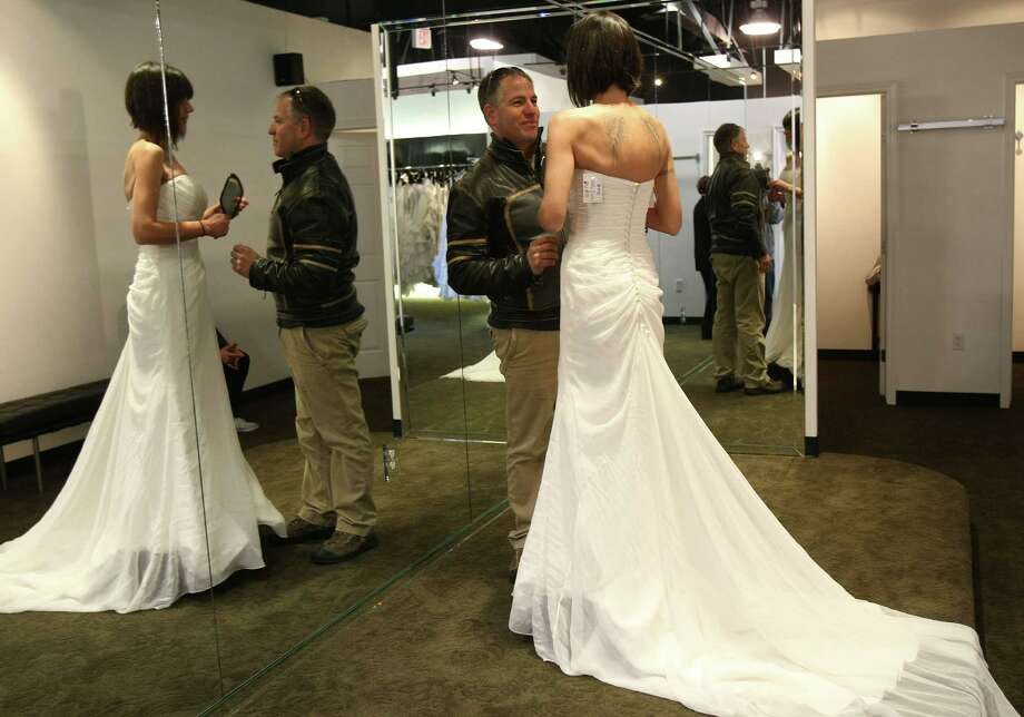 Air Force Master Sgt. Greg Quintana smiles at his bride Karina Quintana as she tries on  a wedding gown at Impression Bridal on Tuesday Jan. 10, 2012.  The bridal salon gave away wedding dresses to women in the military or who are marrying a military man.  The event is being conducted by the salon and Brides Across America, a non profit group that helps provide wedding gowns to the military. Photo: HELEN L. MONTOYA, San Antonio Express-News / SAN ANTONIO EXPRESS-NEWS