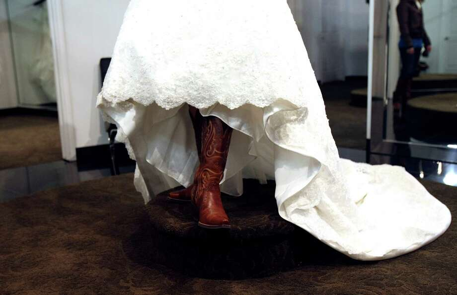 Samantha Templen shows off the boots she  plans to wear with her wedding gown. Templen was among the brides who showed up for the gown giveaway at Impression Bridal on Tuesday Jan. 10, 20122. Women in the military or who are marrying a military man were eligible for to receive a free dess.  The event is being conducted by the salon and Brides Across America, a non profit group that helps provide wedding gowns to the military. Photo: HELEN L. MONTOYA, San Antonio Express-News / SAN ANTONIO EXPRESS-NEWS