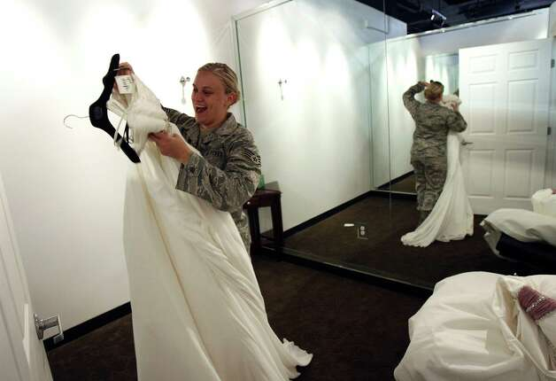 US Air Force Staff Sgt. Dayna Friend tries on a wedding down during as Impression Bridal gave away gowns to women in the military or who are marrying a military man on Tuesday Jan. 10, 2012 .  The event is being conducted by the salon and Brides Across America, a non profit group that helps provide wedding gowns to the military. Photo: HELEN L. MONTOYA, San Antonio Express-News / SAN ANTONIO EXPRESS-NEWS