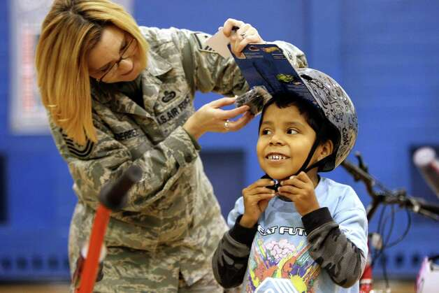 Master Sgt Judith Gutierrez helps Joshua Arnold put on his new helmet as Reservists from the 233rd Airlift Wing from Lackland Air Force Base donated more than 50 bicycles to the Boys and GIrls Club of San Antonio on Friday Dec. 23, 2011.  This is the third year the group has donated bicycles. Photo: HELEN L. MONTOYA, San Antonio Express-News / SAN ANTONIO EXPRESS-NEWS