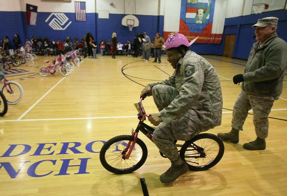 Master Sgt Brian Boyd rides a bicycle into the gym at the Calderon Branch of the Boys and Girls Club on Friday Dec. 23, 2011.  Reservists from the 233rd Airlift Wing from Lackland Air Force Base donated more than 50 bicycles to the Boys and GIrls Club of San Antonio.  This is the third year the group has donated bicycles. Photo: HELEN L. MONTOYA, San Antonio Express-News / SAN ANTONIO EXPRESS-NEWS