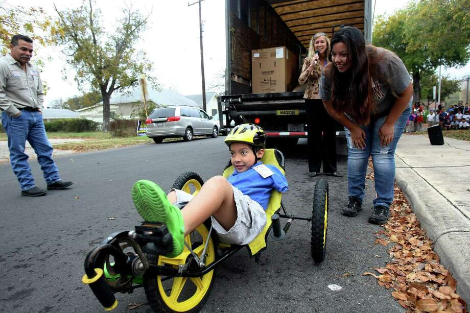 David Cortez a second grader at Herff Elementary School rides a banana peel bike trucked in from the east coast on Thursday Dec. 6, 2012 as his mom Vanessa Amesquita watches. Cortez was born with no arms and cannot ride a traditional bicycle with handlebars. Last month he told school principal Traci Smith he wished he could ride a bike.  While visiting friends in Maryland Smith announced plans to raise $600 to buy the boy a banana peel bike, which has three wheels, a recumbent canvas seat and rests low to the ground. The friend offered to donate a model her children no longer used, if Smith could cover the shipping. As Smith was raising funds for the shipping costs YRC Freight offered to convoy the bike to San Antonio for free. After a nine day journey that began in Ocean City on Nov. 27 the bike arrived on Thursday. Photo: Helen L. Montoya, San Antonio Express-News / ©SAN ANTONIO EXPRESS-NEWS