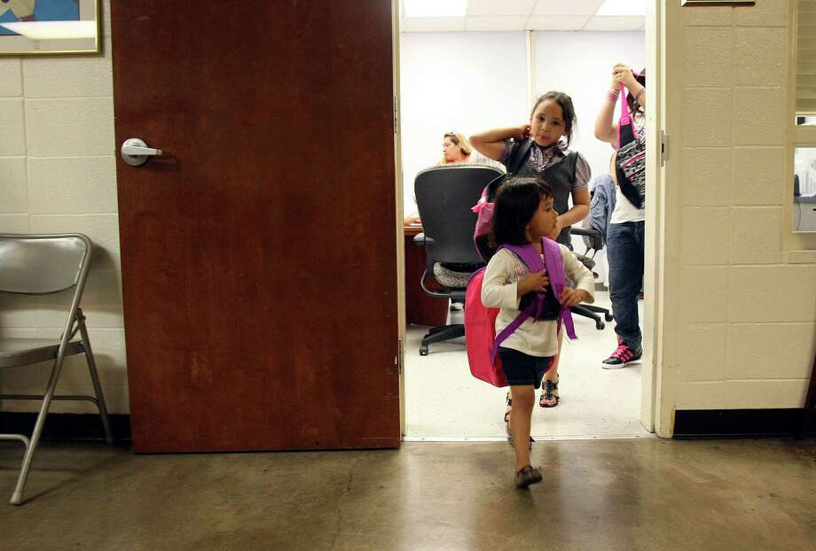 Sarah Garza, 3, and Yesenia DeLeon  wear the new backpacks they received from the Bexar Area Agency on Aging on Friday Aug. 10, 2012.  Ninety five grandparents received $75 school vouchers from the agency at The Neighborhood Place. The grandparents received vouchers for their 286 grandchildren, totaling $20,000, from the agency. Photo: Helen L. Montoya, San Antonio Express-News / ©SAN ANTONIO EXPRESS-NEWS