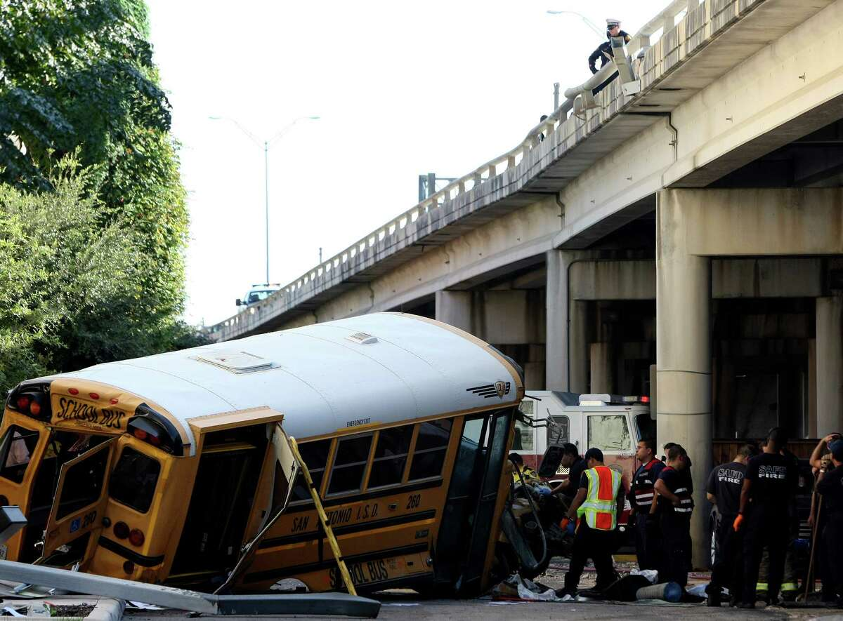 Emergency responders clean up after a collision caused a San Antonio ISD school bus to crash through a guardrail and fall off I-37 near Houston Street. A 7-year-old student and two San Antonio Independent School District staffers were injured.