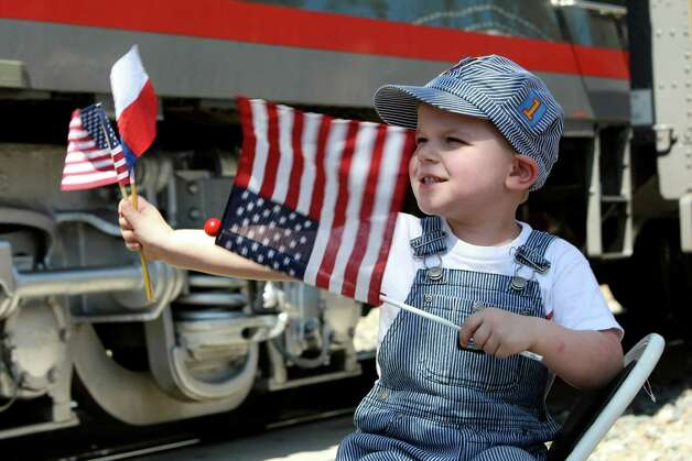 Grady Mueller waves flags as  the Union Pacific's vintage E-9 streamliner diesel locomotive, a sleeker model that took over from the steam engines in the 1950s, leaves the New Braunfels Train museum on Thursday April 19, 2012. Photo: HELEN L. MONTOYA, San Antonio Express-News / ©SAN ANTONIO EXPRESS-NEWS