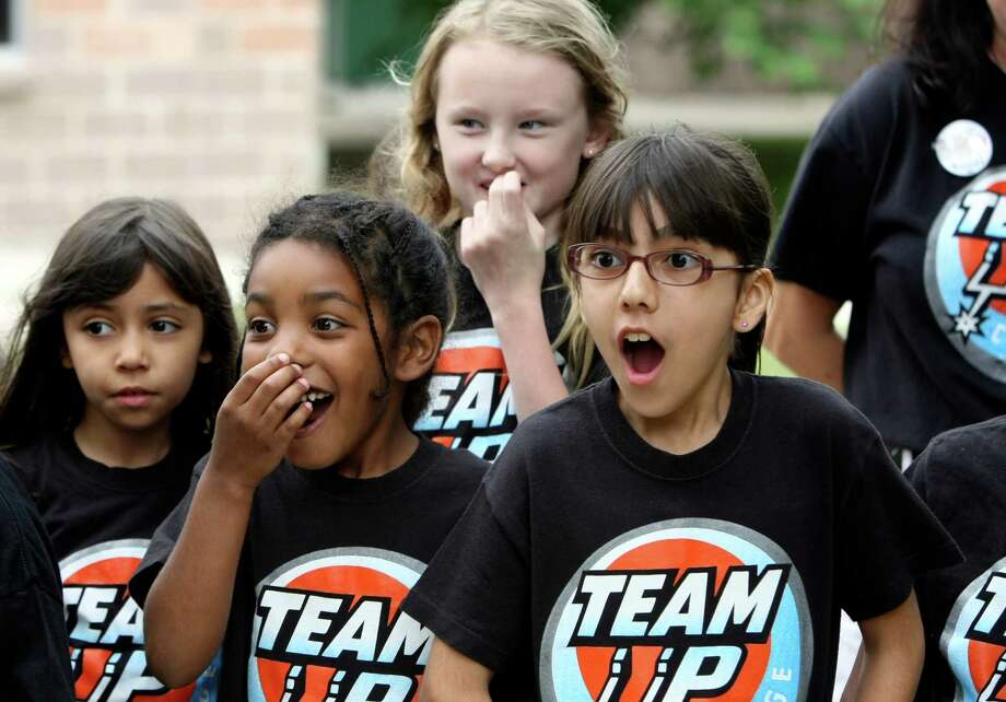 Yanira Saenz, 7, Zehr Williams, 6, Marissa Merriam, 10 and Mayra Rodriguez are surprised by the Spurs Coyotoe during a special presentation at Watts Elementary School on Friday April 13, 2012 as part of the Silver & Black Give Back 2011-2012 Team Up Challenge.  The We Serve Too group, who received the award hosted a toy drive for children in Afghanistan who have been the victims of conflict and are in military hospitals.   They collected more than 200 stuffed animals, 200 boxes of crayons and coloring books.  The group plans to use their award to make Fly-Away Bags for service men and women on deployment, create a scholarship and maintain the club at the school while expanding to the other elementary schools in the Shertz-Cibolo University City School District. Photo: HELEN L. MONTOYA, San Antonio Express-News / ©SAN ANTONIO EXPRESS-NEWS