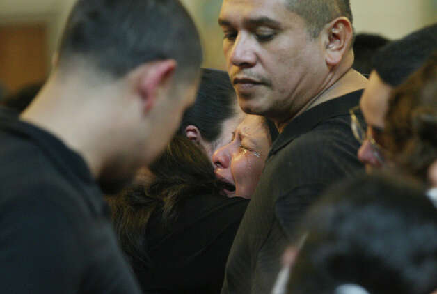 Noralva Gonzalez, center, cries as she and her husband, Jaime Gonzalez Sr., right, parents of 15-year-old Jaime Gonzalez, Jr. mourn his death at Holy Family Church in Brownsville, Texas, Thursday, Jan. 5, 2012. The teenager was shot and killed by Brownsville Police officers when he pointed a gun toward them at Cummings Middle School. Gonzalez was a student at the school. The gun turned out to be a pellet gun. Photo: JERRY LARA, San Antonio Express-News / SAN ANTONIO EXPRESS-NEWS