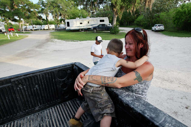 Nicole Garcia hugs her son, Johnny Joe Garcia, III, 3, at the Tips Park in Three Rivers, Texas, Monday, March 26, 2012. In back is her husband, Johnny Joe Garcia, Jr. The family has lived at the park for the past two months due to the lack of housing in the Eagle Ford Shale play counties of South Texas. He is a pipeline trucker in the oil and gas industry. Photo: JERRY LARA, San Antonio Express-News / SAN ANTONIO EXPRESS-NEWS