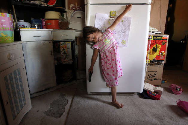 Five-year-old Tomasa Carrizales, 5, plays by the family's refrigerator in Candelaria, Texas, Monday, Feb. 6, 2012. The town is located along the Rio Grande 42 miles southwest of Marfa, Texas. The Presidio County town lost its school in 1998 and students have since been bused over 50 miles to school in Presidio, Texas. Parent participation in school activities is at a minimal with the distance being a hardship. The child's mother, Rosa Carrizales, decided to keep her home instead of sending her to pre-kinder class, because she felt the ride would be too much for her. A Lutheran group is exploring the possibility of opening a charter school in the town. Photo: Jerry Lara, San Antonio Express-News / © San Antonio Express-News