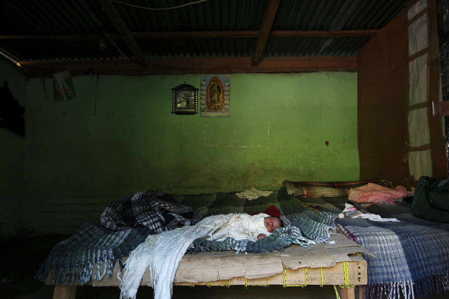 "Under the watch of the Virgin of Guadalupe, a 15-day-old baby girl lies on the family's bed made out of wood and cardboard in Batopilas, Mexico, Saturday, Oct. 6, 2012. Her mother, Maria Reyes Lopez Ortiz, 21, said they still had not named the baby. The town, at the bottom of Batopilas Canyon in Chihuahua, was once a popular tourist destination. With the drug war crisis affecting the area and the rest of the country, tourism has come to a standstill. ""It's a hugh crisis for Batopilas. Tourism supports a lot of people. It's very severe and the government can do very little,"" said city administrator Rafael Gastelum. Photo: Jerry Lara, San Antonio Express-News / © 2012 San Antonio Express-News"