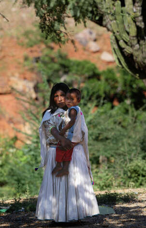 "Chayo Torres, 25, holds her infant son, Daniel, in the settlement of El Arenal de Los Lupes near Batopilas, Mexico, Sunday, Oct. 7, 2012. She had three children, she said, ""uno se me acabo,"" meaning died. The Tarahumara have historically lived through cyclical waves of hunger and Torres had no doubt her community would soon need help. ""It's very bad. I just traded some chili pequins for a kilo of flour. We have some squash and a little corn, but no beans."" Photo: Jerry Lara, San Antonio Express-News / © 2012 San Antonio Express-News"